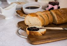 Sliced loaf of bread with currant jam with jar. Cup of tea on background. Healthy breakfast royalty free stock photos