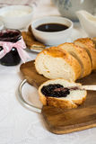 Sliced loaf of bread with currant jam with jar Stock Photo