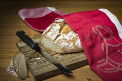 Sliced loaf of bread on wooden cutting board Stock Photos