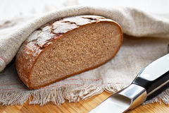 Sliced loaf of gray floured bread and knife Stock Images