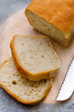 Sliced loaf of homemade  bread on cooking paper Stock Images