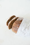 Sliced loaf of homemade bread in a paper on a white background with space for your text. Stock Photos