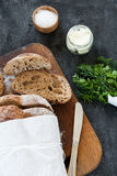 Sliced loaf of homemade bread, with salt, herbs and butter on a dark background. Daylight, space for your text. Stock Photos
