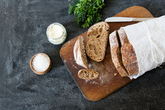 Sliced loaf of homemade bread, with salt, herbs and butter on a dark background. Daylight, space for your text. Stock Image
