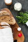 Sliced loaf of homemade bread, with salt, herbs and butter on a dark background. Daylight, space for your text. Sliced loaf of homemade bread, with salt, herbs Stock Photo