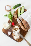 Sliced loaf of homemade bread, with salt, radish, herbs and butter on a white background. Stock Photo