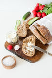 Sliced loaf of homemade bread, with salt, radish, herbs and butter on a white background. Stock Image