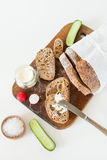 Sliced loaf of homemade bread, with salt, radish, herbs and butter on a white background. Royalty Free Stock Images