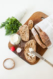 Sliced loaf of homemade bread, with salt, radish, herbs and butter on a white background. Stock Photos