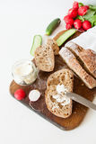Sliced loaf of homemade bread, with salt, radish, herbs and butter on a white background. Daylight, space for your text Stock Photos
