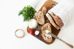 Sliced loaf of homemade bread, with salt, radish, herbs and butter on a white background. Daylight, space for your text Royalty Free Stock Photos