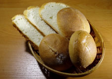 Sliced loaf and and round slider buns in wicker breadbasket Stock Photos