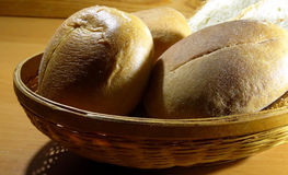 Sliced loaf and and round slider buns in wicker breadbasket Royalty Free Stock Photography