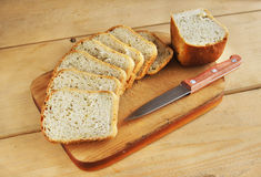 Sliced loaf on a wooden cutting board. Sliced loaf on a cutting board on a wooden table Royalty Free Stock Images