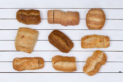 Sliced loaves of bread neatly aligned. Assortment of nine different sliced loaves of bread neatly aligned on a white wood table viewed from above stock image