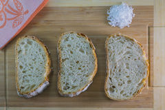 Sliced Maia Bread and Salt. Three slices of maia sourdough bread and coarse salt on wooden cutting board Stock Photo