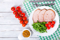 Sliced meat with arugula salad, cherry tomatoes, top view, close Stock Photos