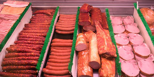 Sliced Meat at a deli counter. A Variety of sausages and hams at a deli counter at a local market royalty free stock photo