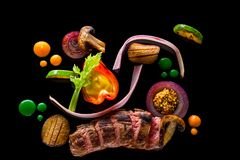 Sliced meat with fresh herbs, vegetables and spices on black background, top view Royalty Free Stock Photos