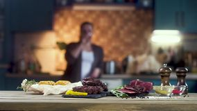 Sliced meat, grilled meat for burgers, corn and spices. Standing on the table. In the background, a young girl is out of focus dri. Nking wine stock video