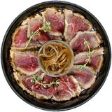 sliced meat with onion on the plate over white Royalty Free Stock Photography