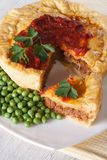 Sliced meat pie and green pea. Vertical close-up Royalty Free Stock Image