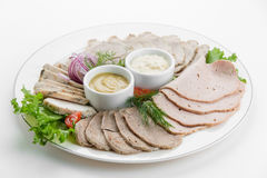 Sliced meat plateau ham with sauces and salad on white plate Royalty Free Stock Photo