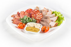 Sliced  meat with vegetables. On white plate Royalty Free Stock Photography
