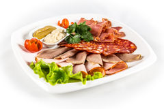Sliced  meat with vegetables. On white plate Stock Images