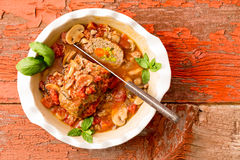 Sliced meatloaf in a casserole on a rustic table Stock Images