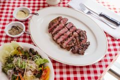 Sliced medium rare charcoal grilled wagyu Ribeye steak in white plate on red and white pattern tablecloth with salad and cutlery Royalty Free Stock Photos