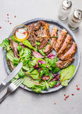 Sliced medium rare grilled barbecue steak and green salad on stone plate with cutlery Royalty Free Stock Photography