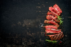 Sliced medium rare grilled beef ribeye steak. On dark background Royalty Free Stock Photo
