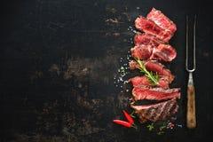 Sliced medium rare grilled beef ribeye steak. On dark background Stock Image