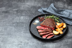 Sliced medium rare grilled beef steak and potato wedges stock image