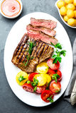 Sliced medium rare grilled beef steak served on white plate with tomato salad and potatoes balls. Barbecue, bbq meat stock image