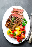 Sliced medium rare grilled beef steak served on white plate with tomato salad and potatoes balls. Barbecue, bbq meat royalty free stock image