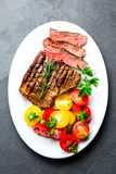 Sliced medium rare grilled beef steak served on white plate with tomato salad and potatoes balls. Barbecue, bbq meat royalty free stock photos