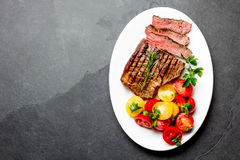 Sliced medium rare grilled beef steak served on white plate with tomato salad and potatoes balls. Barbecue, bbq meat. Beef tenderloin. Top view, slate Royalty Free Stock Photography