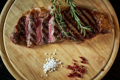 Sliced medium rare grilled steak on rustic cutting board with rosemary and spices , dark rustic metal background, top royalty free stock photo