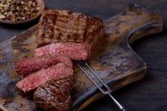 Sliced medium rare grilled steak. On cutting board stock photos