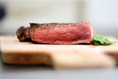 Sliced medium rare grilled steak on wooden cutting board with green leafs and spices Royalty Free Stock Photo