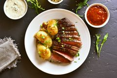 Sliced medium rare roast beef with potato. Over black stone background. Top view, flat lay Royalty Free Stock Photo