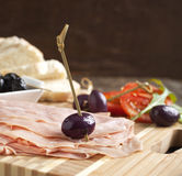 Sliced mortadella with bread, tomato and olives Stock Photos
