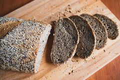 Sliced multigrain homemade bread on a wooden cutting board at home stock image