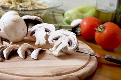 Sliced mushrooms. Fresh sliced mushrooms on a circular wood with bowl of pasta, tomatoes,olive oil,and pepper in the background stock photos