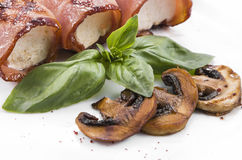 Sliced mushrooms champignon cooked on grill and bacon roll Royalty Free Stock Images