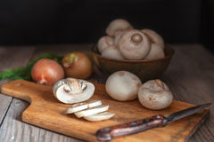 Sliced mushrooms closeup, lying on wooden cutting board with knife. Sliced mushrooms closeup, lying on a wooden cutting board with a knife. Plate with royalty free stock image