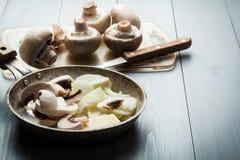 Sliced mushrooms with onion on a pan Stock Photos
