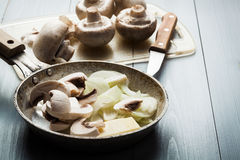 Sliced mushrooms with onion on a pan Royalty Free Stock Images